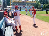 Reilly Johnson (sitting), Tanner Kirwer (#19) and Justin Watts (#25) hang out near the home dugout.